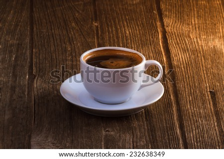 Coffee cup and coffee beans on old wooden