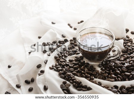 coffee cup and coffee beans on white cloth.beautiful background/ selective focus - stock photo