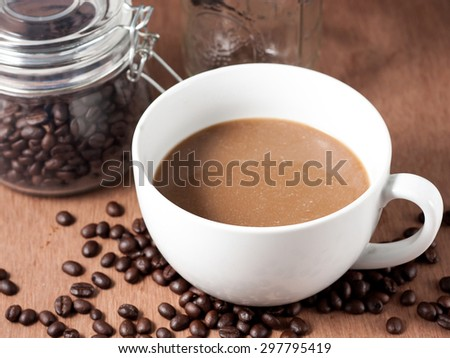 Coffee cup and coffee beans on wood background - stock photo