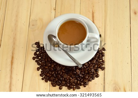 coffee cup and coffee beans on wooden - stock photo