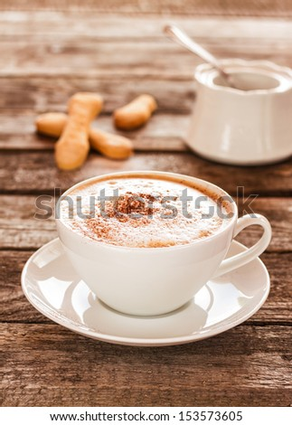 Coffee cup and cookies on an old vintage planked wood table - moody still life - stock photo