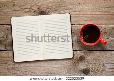Coffee cup and diary on wooden background - stock photo