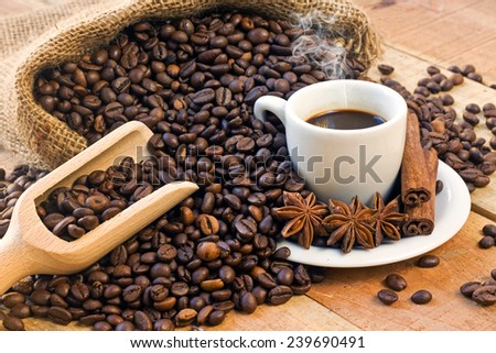 coffee cup and grains on wooden table - stock photo