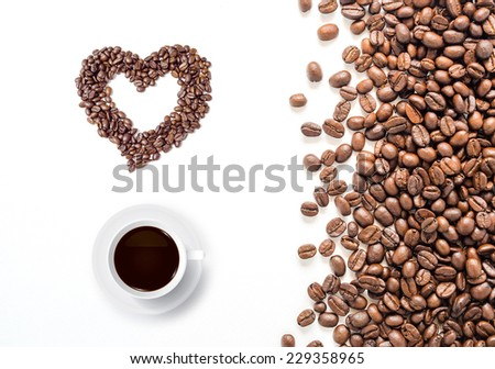 Coffee cup and heart of coffee beans on white background. - stock photo