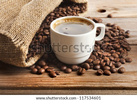 coffee cup and  jute sack close-up on wooden table background - stock photo