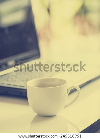 Coffee cup and laptop for business, Selective focus on coffee and using filter photo effect. - stock photo