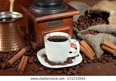 Coffee cup and metal turk on wooden background - stock photo