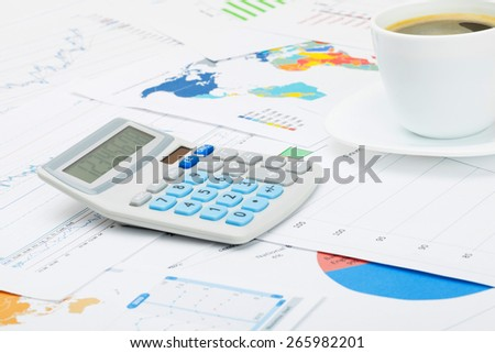 Coffee cup and neat calculator over different charts - stock photo