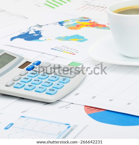 Coffee cup and neat calculator over different charts - close up shot - stock photo