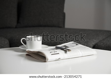 Coffee cup and newspaper on the table - stock photo