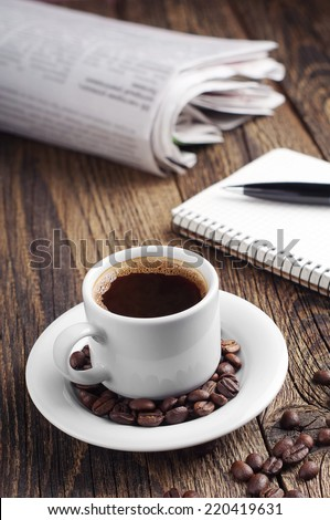 Coffee cup and newspaper on vintage wooden table - stock photo