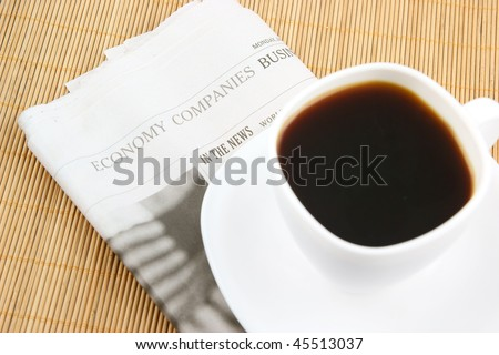 Coffee cup and newspaper on wooden background