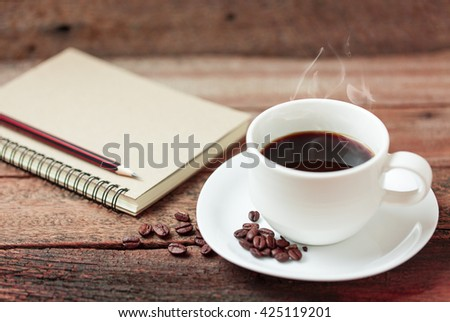 Coffee cup and note book on a wooden table. - stock photo
