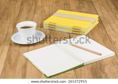 coffee cup and notebook on wooden background,vintage picture - stock photo