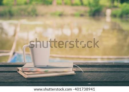 Coffee cup and notebooks on rustic wood table at outdoor area with rural lake view on blurry background in morning time with vintage filter effect