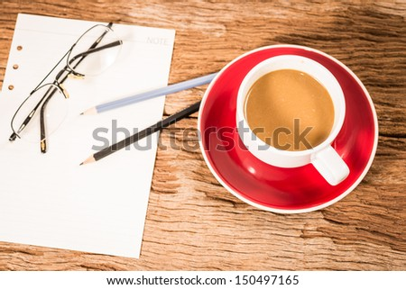 Coffee Cup and office supplies on old wood table - stock photo
