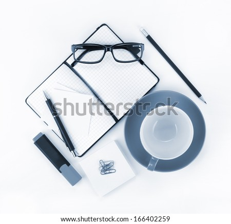 Coffee cup and office supplies. View from above. Blue toned - stock photo