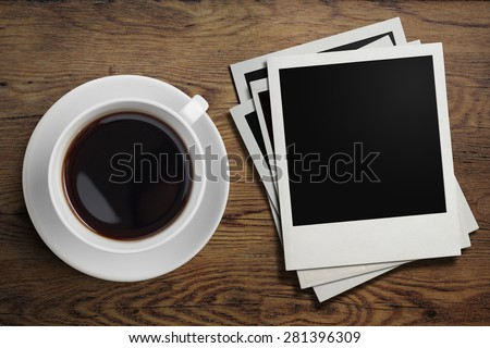 coffee cup and polaroid photo frames on table - stock photo