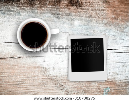 coffee cup and retro photo over grunge wood background