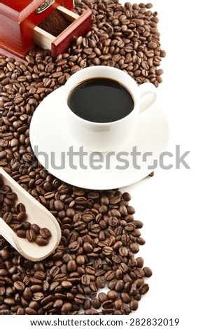 Coffee cup and saucer and winnower with minced and spilled coffee - stock photo