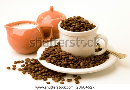 Coffee cup and saucer filled and surrounded with coffee beans next to a creamer set with cream and sugar on white background - stock photo