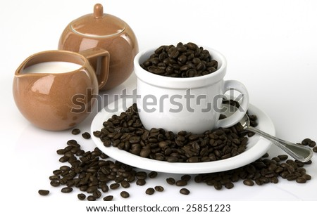 Coffee cup and saucer filled to overflowing with coffee beans, creamer set on the side - stock photo