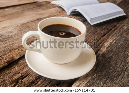 Coffee cup and saucer on a old wooden with book.