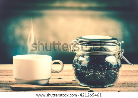 Coffee cup and saucer on a wooden table. Dark background in vintage tone - stock photo