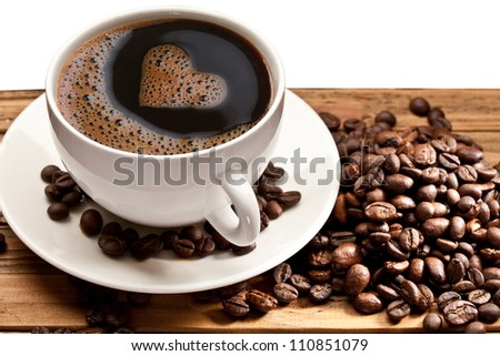 Coffee cup and saucer on a wooden table. Foam in the form of the heart. - stock photo