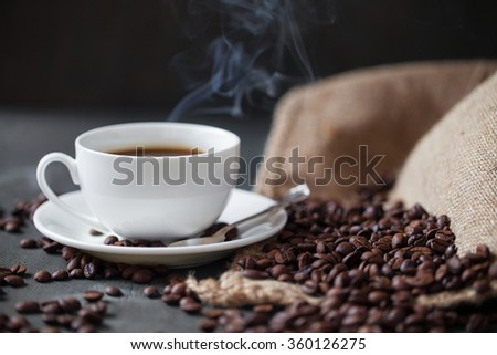 Coffee cup and saucer on a wooden table. Grey background. - stock photo