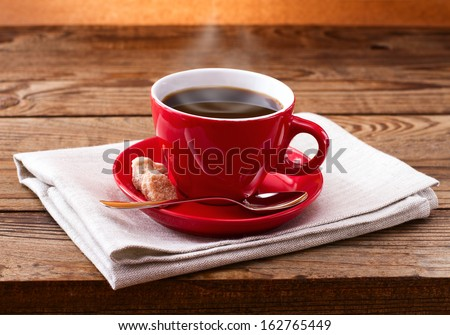 Coffee cup and saucer on  wooden table. Dark background. - stock photo