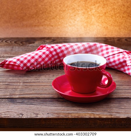 Coffee cup and saucer, tablecloth on wooden table. Dark background. Coffee concept. Selective focus. - stock photo