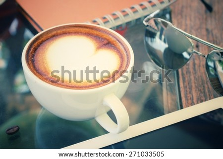 Coffee cup and tablet with sun glasses - stock photo