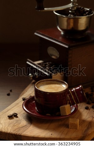 Coffee cup and vintage coffee grinder - stock photo