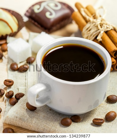 Coffee cup, beans, chocolate candy, cinnamon, sugar and anise on a table