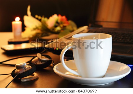 coffee cup beside laptop and headphone