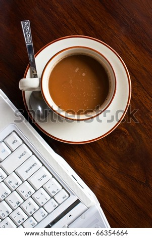 Coffee cup beside notebook on working table - stock photo