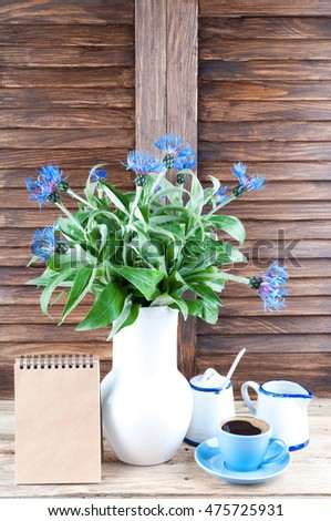 Coffee cup, bouquet of cornflowers and notebook on wooden background with copy space. Coffee break in the kitchen. Summer flowers