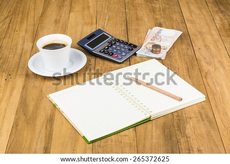 coffee cup ,calculator and notebook on wooden table - stock photo