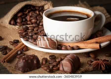 Coffee cup, chocolate and beans on a rustic background. Coffee Espresso. Cup Of Coffee, anise, cinnamon and coffee beans on table. - stock photo