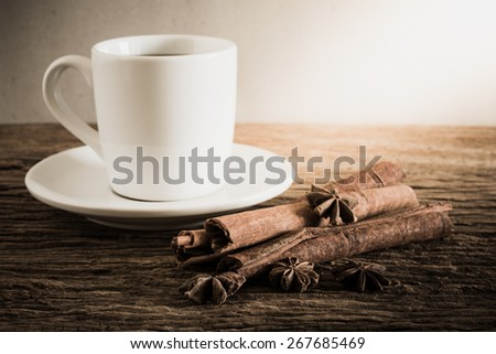 coffee cup, cinnamon sticks on wooden table with against grunge wall. vintage tone , Focus at spice - stock photo