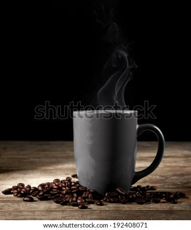 coffee cup, coffee beans and cinnamon sticks on dark background - stock photo