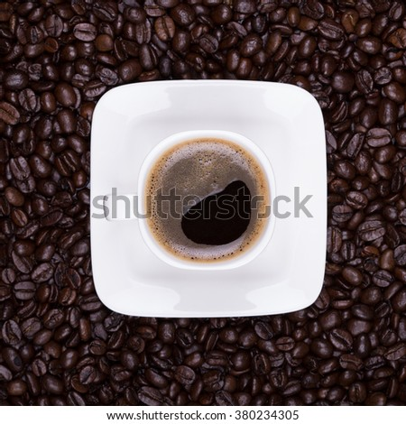Coffee cup. Coffee beans background. Square. Top view. Cup of coffee. White cup with saucer. - stock photo