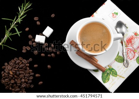 Coffee cup, coffee beans, cinnamon sticks and sugar on black background - stock photo
