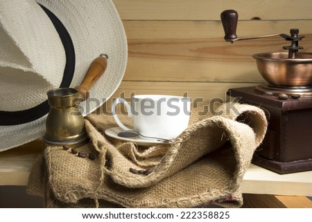 Coffee cup, coffee grinder, coffee brewing arabian Cezve, burlap, coffee beans on a wooden shelf.