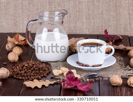 Coffee cup, cream, coffee grains and cane sugar on a table - stock photo
