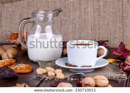 Coffee cup, cream, coffee grains and oatmeal cookies on a table - stock photo