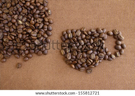 Coffee cup create by coffee beans on  grunge wooden board background