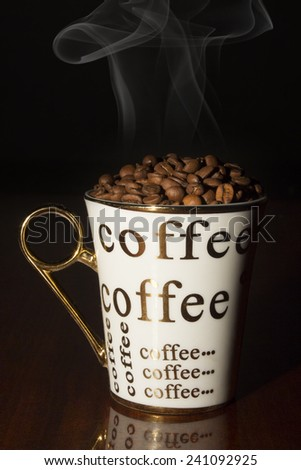 Coffee cup filled with coffee beans on a table 2 - stock photo