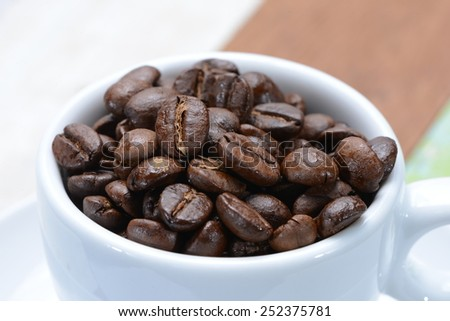 Coffee cup filled with coffee beans. Very shallow focus on coffee beans in cup. - stock photo